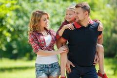 在步行的愉快的家庭在公园在夏天 库存照片