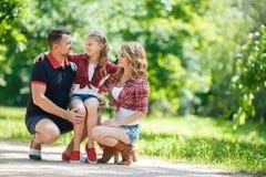 在步行的愉快的家庭在公园在夏天 免版税库存图片