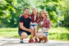 在步行的愉快的家庭在公园在夏天 免版税图库摄影