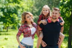 在步行的愉快的家庭在公园在夏天 图库摄影