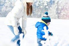 在步行的愉快的家庭在晴朗,多雪的天-寒假 图库摄影