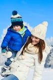 在步行的愉快的家庭在晴朗,多雪的天-寒假 库存图片