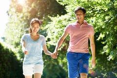 在步行的浪漫亚洲夫妇在乡下 免版税库存图片