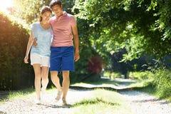 在步行的浪漫亚洲夫妇在乡下 免版税库存照片