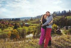 在步行的爱恋的年轻夫妇在五颜六色的秋天在山村环境美化 库存图片