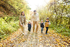 在步行的美丽的年轻家庭在秋天森林里 免版税库存图片