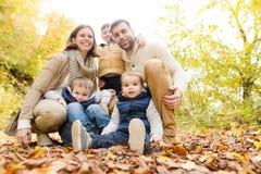 在步行的美丽的年轻家庭在秋天森林里 库存照片