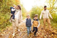 在步行的美丽的年轻家庭在秋天森林里 图库摄影
