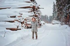 在步行的逗人喜爱的愉快的儿童女孩画象在有砍树的冬天森林里在背景 免版税库存照片