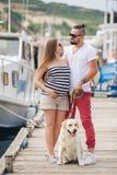 在步行的年轻夫妇在有狗的港口 免版税库存图片