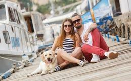 在步行的年轻夫妇在有狗的港口 库存照片