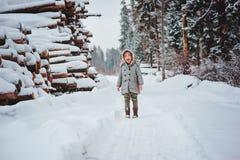 在步行的滑稽的愉快的儿童女孩画象在有砍树的冬天多雪的森林里在背景 免版税库存图片