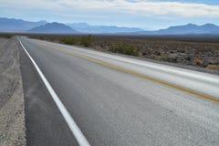 在死亡谷沙漠蓝色山脉的高速公路 库存图片