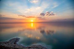 在死海的从约旦的日落,犹太看法向以色列和山  太阳、天空和云彩的反射 咸海滩,盐 免版税库存图片