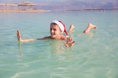在死海的愉快的小的圣诞老人 库存照片