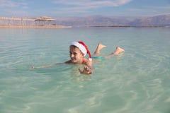 在死海的愉快的小的圣诞老人 库存图片
