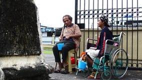 在残疾叫化子旁边的盲人在教会围场寻找施舍的门门户的轮椅的 股票视频