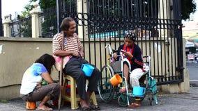 在残疾叫化子旁边的盲人在教会围场寻找施舍的门门户的轮椅的 影视素材