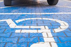 在残疾热忱的停车场的两个轮子标记用蓝色轮椅标志 库存照片