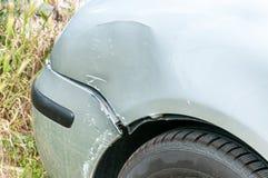在残破和损坏的银色汽车击毁附近车灯的前方在崩溃事故的与在碰撞关闭的被抓的油漆 库存照片