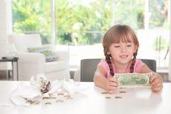 在残破的存钱罐附近的逗人喜爱的小女孩 库存照片