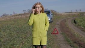 在残破的汽车附近的哀伤的迷人的女商人在农村路拜访手机 慢的行动 股票视频