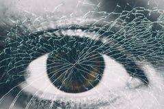 在残破的玻璃后的一只女性眼睛 免版税库存照片