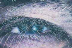 在残破的玻璃后的一只男性眼睛 免版税库存图片