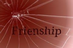 在残破的玻璃的文本友谊 争吵或冲突概念 库存照片