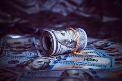 在残破的金钱的黑暗是美元卷  免版税库存照片