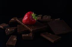 在残破的巧克力块的一个草莓 免版税库存照片