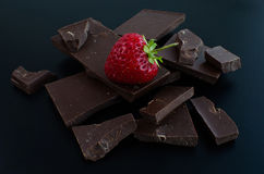 在残破的巧克力块的一个草莓 库存照片
