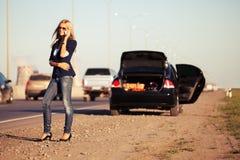 在残破的汽车旁边塑造妇女拜访手机的 免版税库存图片