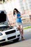 在残破的汽车附近的妇女要求帮助 图库摄影