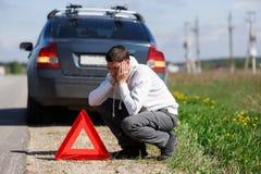在残破的汽车附近的沮丧的人 免版税库存图片
