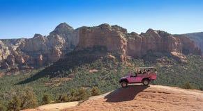 在残破的箭头足迹的一次桃红色吉普游览 库存图片