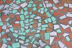 在残破的陶瓷砖地板上的老五颜六色的马赛克  免版税库存图片