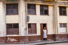 在殖民地大厦之外的一个年长夫人在老哈瓦那,古巴 库存图片