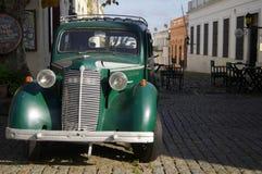在殖民地街道的老绿色汽车 库存照片
