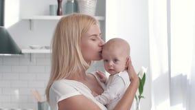 在母亲、愉快的父母拥抱女孩和神色的手上的新生儿在照相机在厨房 股票视频