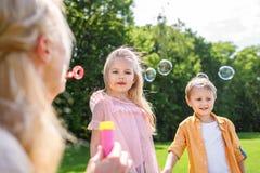 在母亲吹的肥皂泡的选择聚焦,当花费与孩子时的时间 库存图片