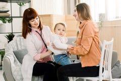 在母亲手上的哭泣的病的孩子女婴在医院或在家和有女性GP的医生考试 库存照片