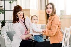 在母亲手上的哭泣的病的孩子女婴在医院或在家和有女性GP的医生考试 免版税库存照片
