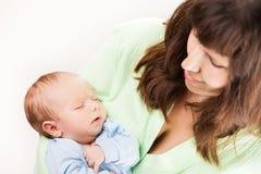 在母亲手上的逗人喜爱的睡觉的新出生的小孩子 免版税库存照片