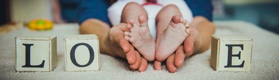 在母亲现有量的婴孩英尺 在女性心形的手特写镜头的微小的新出生的婴孩` s脚 图库摄影
