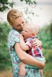 在母亲的手上的打呵欠的男孩 库存图片