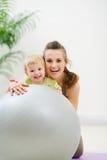 在母亲纵向微笑之后的婴孩球 免版税库存照片