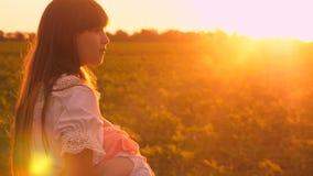 在母亲,婴孩的胳膊的儿童哈欠在公园要睡觉,走妈妈和女儿在日落在夏天 影视素材