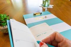 在每周计划者的妇女文字在早晨阳光-仅手下 免版税图库摄影