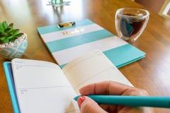 在每周计划者的妇女文字有绿松石的上色了笔 库存图片